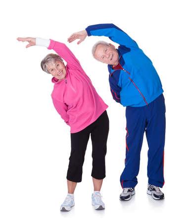 stretching: Retrato de un par mayor que ejercita en el fondo blanco Foto de archivo