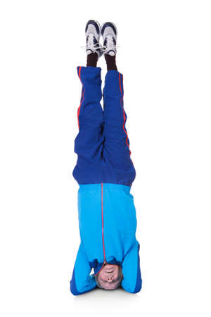 headstand: Senior Man Performing Yoga Headstand On White Background