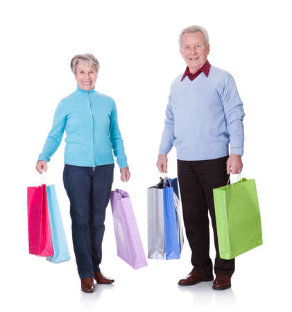Portrait Of Happy Senior Couple Holding Shopping Bags photo