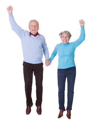 Portrait Of Senior Couple Jumping In Joy Over White Background photo
