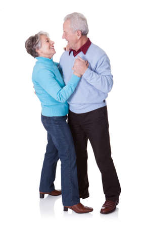 male senior adult: Portrait Of Senior Couple Dancing On White Background Stock Photo