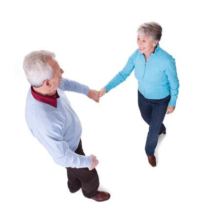 Portrait Of Senior Couple Dancing On White Background photo