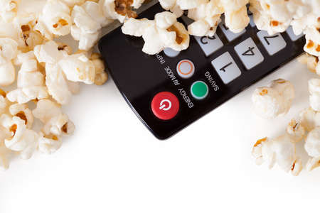 remote communication: Close-up Of Remote Control And Popcorn Over White Background Stock Photo