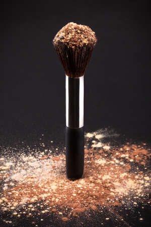 Makeup Brush And Cosmetic Powder Isolated On Black Background photo