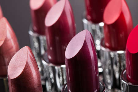 lipstick: Lipsticks In A Row Isolated Over Gray Background Stock Photo