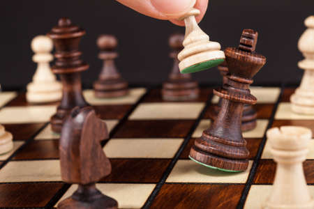 Close-up Of Hand Playing Chess And Falling King photo