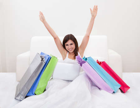 e shop: Young Woman Sitting On Bed And Shopping Online Stock Photo