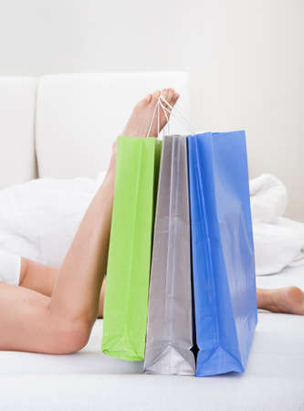 shoppingbags: Close-up Of Womans Leg Holding Shoppingbags On Bed