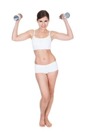 Happy Young Woman Working Out With Dumbbells On White Background photo