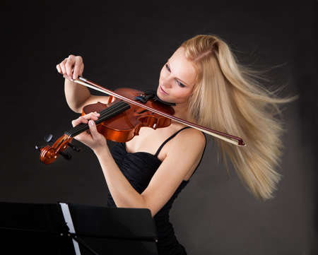 passionately: Young woman passionately playing violin over black background Stock Photo