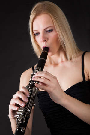 woodwind instrument: Beautiful young woman playing clarinet over black background Stock Photo