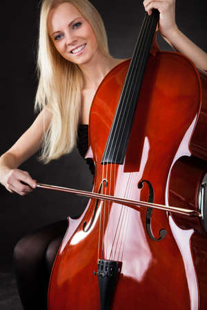 Beautiful young woman playing cello over black background Stock Photo - 18906425