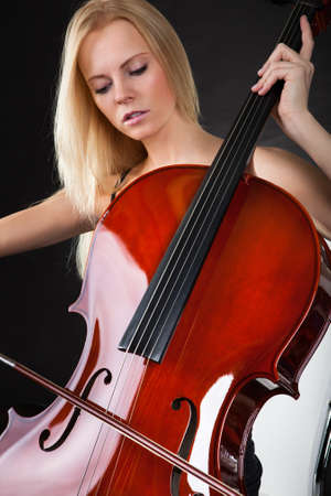 Beautiful young woman playing cello over black background Stock Photo - 18906420