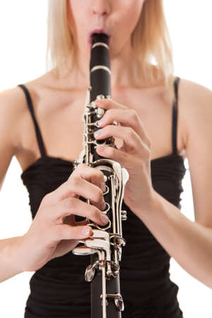 Beautiful young woman playing clarinet over black background photo