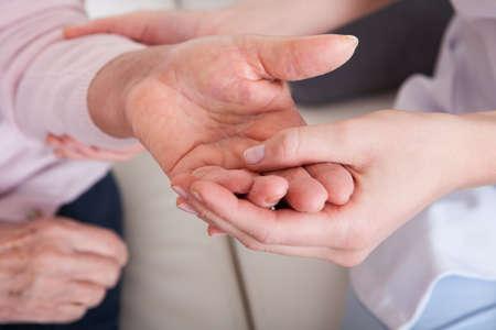 artritis: Mujer joven con manos de mujer mayor; Indoor