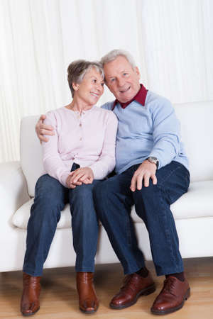 Portrait de l'heureux s�ance Senior Couple sur canap� photo