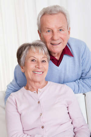 embracement: Portrait Of Happy Senior Couple Sitting On Couch