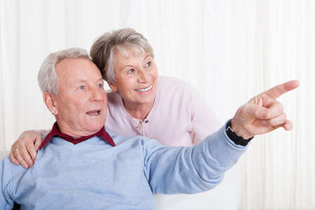 Portrait Of Happy Senior Couple Gesturing And Sitting On Couch photo