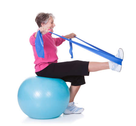 physical: Senior Woman Stretching Exercising Equipment On White Background Stock Photo