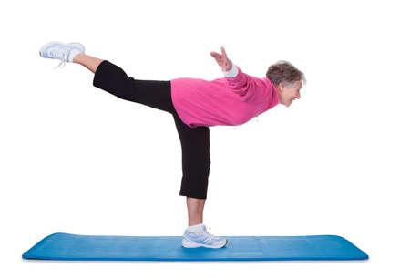 one senior: Senior Woman Standing On One Leg And Exercising Over White Background Stock Photo