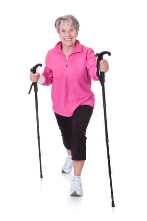 tracksuit: Senior Woman Walking With Hiking Poles On White Backgrounds