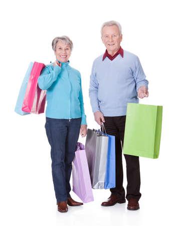 older couple: Portrait Of Happy Senior Couple Holding Shopping Bags Stock Photo