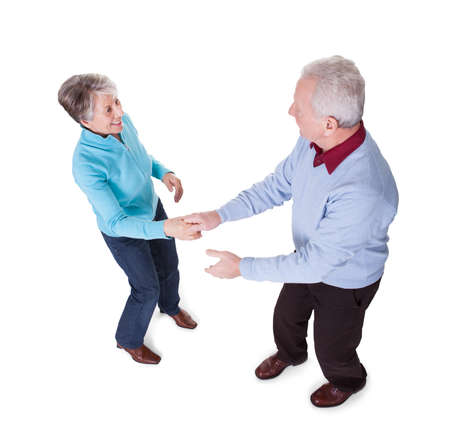 Portrait Of Senior Couple Dancing On White Background photo