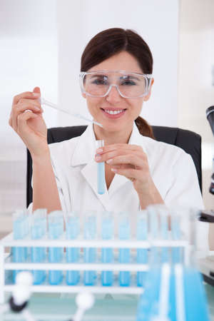 Female With Protective Glasses Holding Chemical Test Tube photo