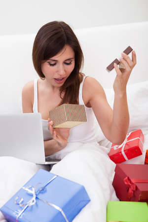Young Woman Surprised By Opening Gift Indoor Stock Photo - 18882804