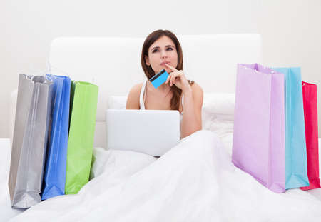 e shopping: Young Woman Sitting On Bed And Shopping Online Stock Photo