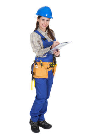 Portrait Of Young Female Worker Writing On Clipboard photo