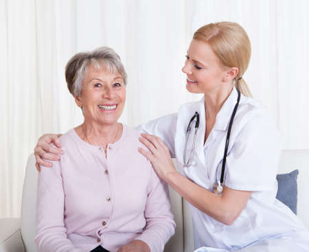 Portrait Of Young Doctor And Senior Patient Sitting On Couch Stock Photo - 18907267