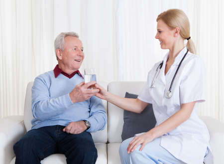 doctor giving glass: Caring Doctor Giving Water To Senior Patient; Indoor Stock Photo