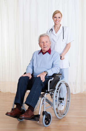 Caring Doctor Helping Handicapped Senior Patient Indoors photo