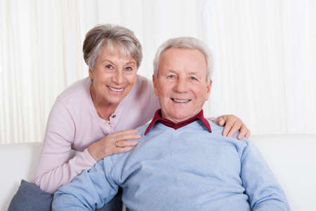 Portrait Of Happy Senior Couple Sitting On Couch photo
