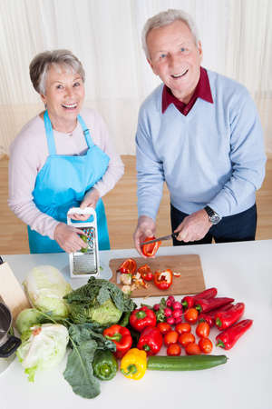 Happy Senior Couple Cutting Vegetables In Kitchen photo