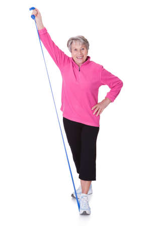 rubber band: Senior Woman Stretching Exercising Equipment On White Background Stock Photo