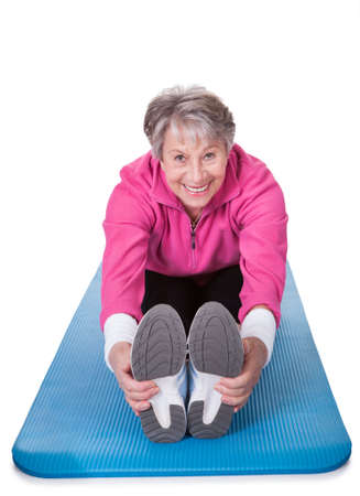 Happy Senior Woman Stretching Her Legs On White Background photo
