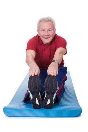 one senior man only: Happy Senior Man Stretching His Legs On White Background Stock Photo