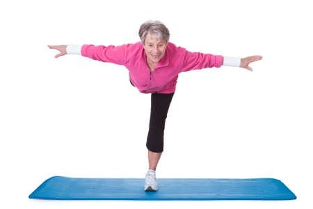an active: Mujer mayor que se coloca en una pierna y el ejercicio sobre el fondo blanco
