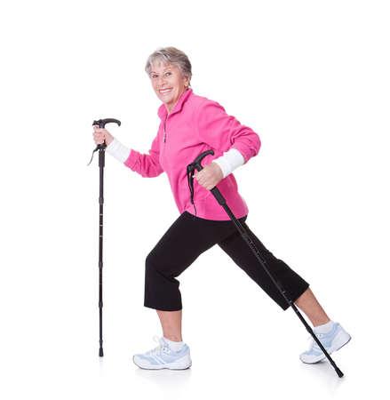 exercitation: Senior Woman Walking With Hiking Poles On White Backgrounds