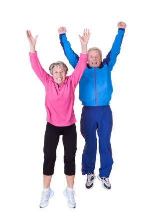 Portrait Of Senior Couple Jumping In Joy Over White Background Фото со стока