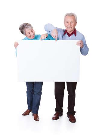 mujeres mayores: Feliz pareja mayor que sostiene el cartel en blanco sobre fondo blanco