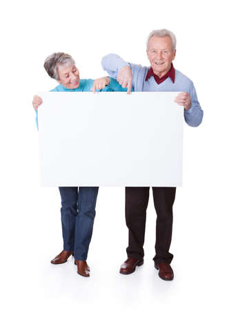 older couples: Happy Senior Couple Holding Blank Placard On White Background