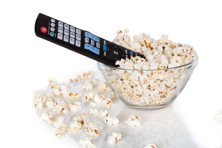 bowl of popcorn: Close-up Of Remote Control In Bowl Of Popcorn Over White Background