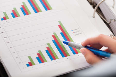 growing business: Close-up Photo Of Hand And Financial Graph Stock Photo