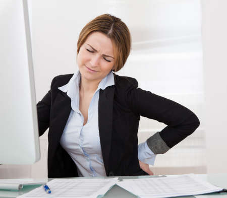 uncomfortable: Business Woman With Back Pain Holding Her Aching Hip Stock Photo