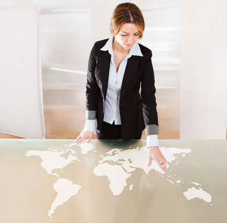 Woman Pointing On Transparent Screen Showing World Map photo