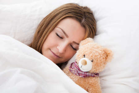 Young Beautiful Woman Sleeping On Bed With Her Teddy Bear photo