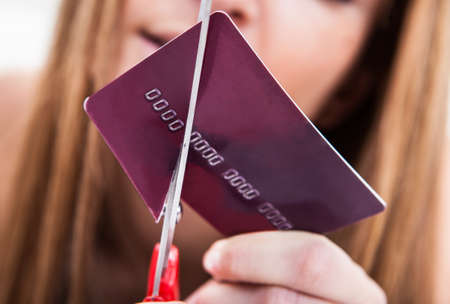 key card: Close-up Of Hand Cutting Credit Card With Scissor